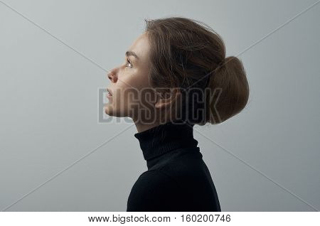 Dramatic Portrait Of A Young Beautiful Girl With Freckles In A Black Turtleneck On White Background