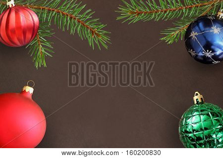 Dark background with Christmas fir branch red wavy dull green ribbed and blue ball