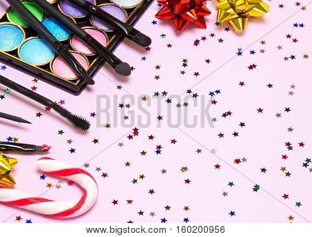 Makeup for holiday party. Red lipstick, liquid eyeliner, mascara, color glitter eyeshadow, brushes, applicator with candy cane, gift wrap bows and confetti. Copy space