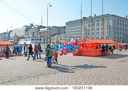 HELSINKI, FINLAND - APRIL 10, 2010: People on The Market Square near food stalls and cafes. On the background is Floating Restaurant Nicolas II and The Old Market Hall next to the Gulf of Finland.