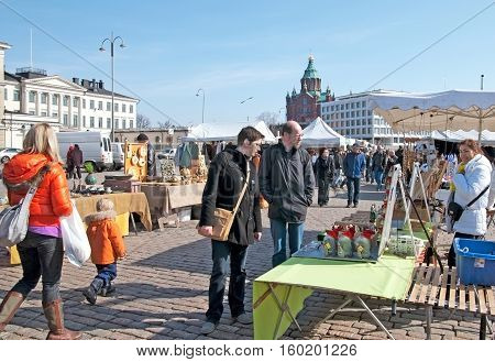 HELSINKI, FINLAND - APRIL 10, 2010: People on The Market Square look at the traditional Finnish souvenirs on the stalls. On the background is The Uspenski Cathedral