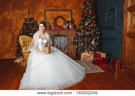 Hands with gift box on the wedding celebration. Studio portraits of beautiful bride with gift .Bride Holding Gift