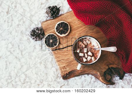 Winter homely scene. Warm red knit sweater and cup of cocoa with marshmallows on wooden tray in bed. Lazy cold weekend.