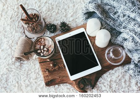 Winter homely scene, scandinavian style. Warm knit sweater, tablet pc with blank screen, candles, cup of sweet cocoa with marshmallows and other decor on wooden tray in bed. Lazy cold weekend.