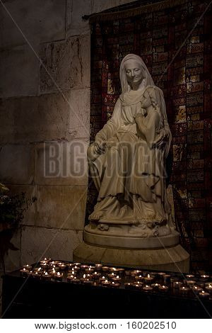 JERUSALEM ISRAEL - APRIL 4: Statues of St. Anne and the young Virgin Mary with lighted candles at the foot of the sculpture in the Church of St. Anne in Old City of Jerusalem Israel on April 4 2015