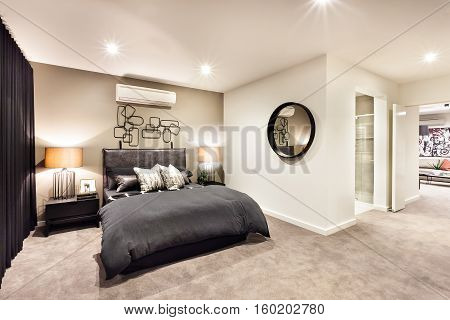 Modern bedroom with a round mirror and hallway through the luxury house