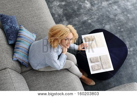 Shopping coverings. Interior design, choice of carpet. Decoration of houses. Woman chooses carpet picker sitting on the sofa in the living room