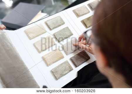 Shop carpets. Picker carpet. Woman in shop with carpets chooses carpet probe.