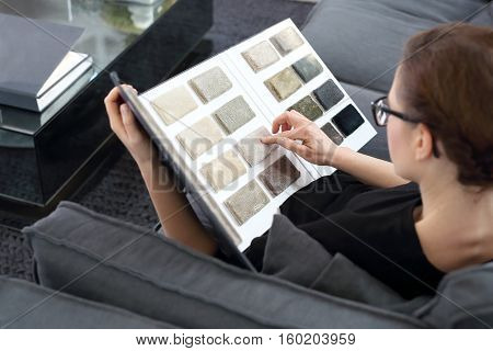 Interior designer with the probe carpetsInterior decorating, shopping carpet. Arranging home shopping coverings Woman chooses carpet for the living room.