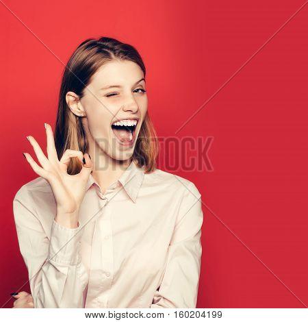 Winking Girl Shows Ok Gesture