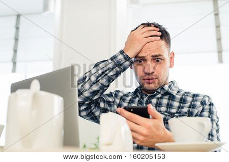 Worried shoked man looking on laptop at cafe.