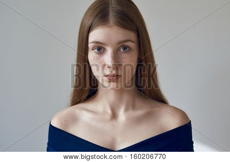Beauty Theme: Portrait Of A Beautiful Young Girl With Freckles On Her Face And Wearing A Blue Dress
