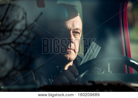 man in his car behind wheel front view through the glass reflection of trees and sky in glass