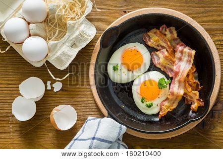 American breakfast with sunny side up eggs, bacon, wood background