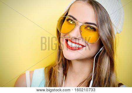 Beauty portrait of a modern young woman in beanie and sunglasses. Youth style, beauty. Hipster style. Red lips style.