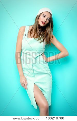 Fashion shot of a modern young woman wearing light blue dress and white beanie hat. Youth style, beauty. Hipster style.