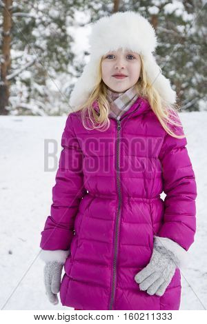 In winter the snow-covered forest stands blond girl in a pink coat.