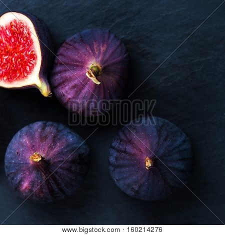 Fresh figs on black background. Beautiful blue violet figs with empty copyspace close up