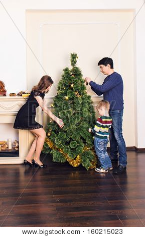 family x-mas winter holidays and people concept - mother father and child decorating christmas tree at home.