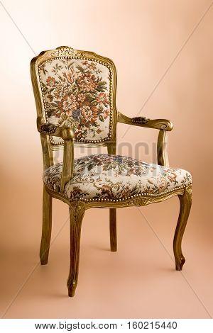 Gold vintage luxury armchair at beige background