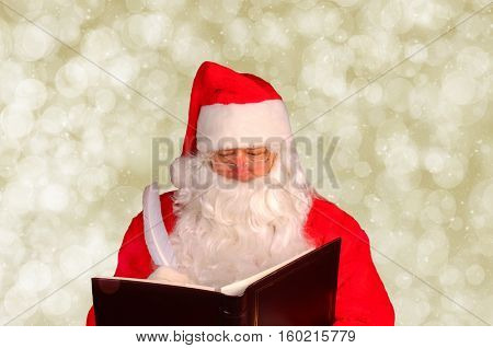 Closeup of Santa Claus writing in his Naughty and Nice Book. Horizontal format with gold bokeh background.