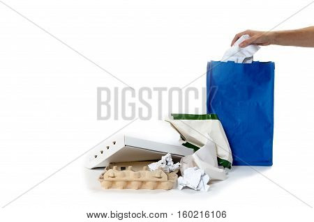 Pile of paper waste is lying on the white background. Woman's hand is inserting used paper into an empty blue bag. All potential trademarks are removed.