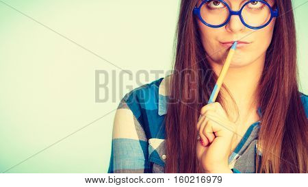 Nerdy Thinking Woman In Glasses Holding Pen