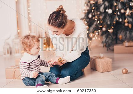 Stylish mother playing with baby girl over Christmas tree in room. Sitting on floor with Christmas decorations. Togetherness. 20s. Family time.