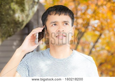 Happy Hipster Man Walking In Autumn Park Using Mobile Phone