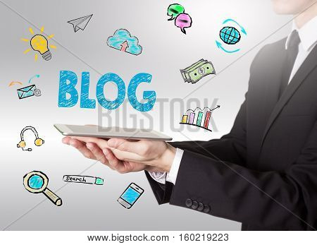 Blog concept, young man holding a tablet computer.