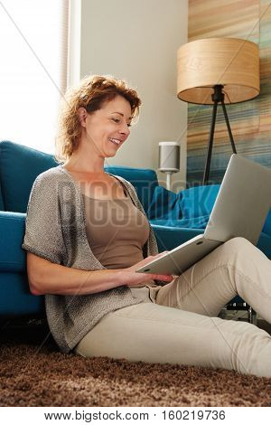 Woman Sitting On Floor In Apartment With Laptop