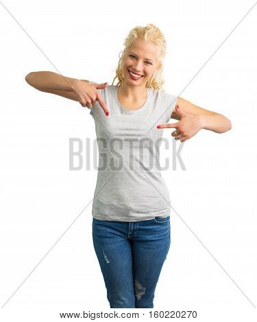 Woman in grey round neck T-shirt pointing at it with both hands