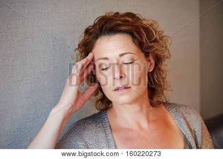 Middle Aged Woman With Hand To Head In Pain