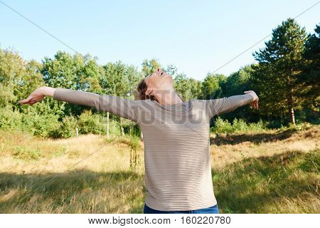 Carefree Older Woman With Arms Outstretched