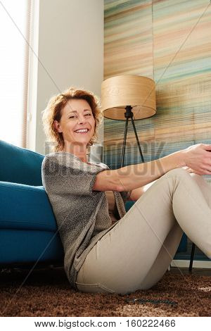 Happy Older Woman Sitting On Floor Of Cozy Apartment