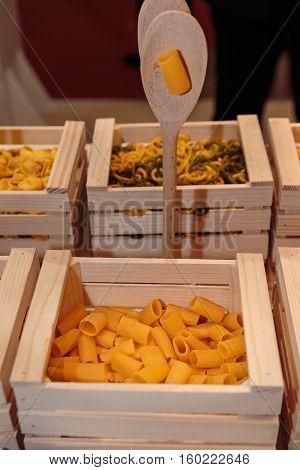 Rigatoni Italian Pasta In Wooden Box With Brown Ladle