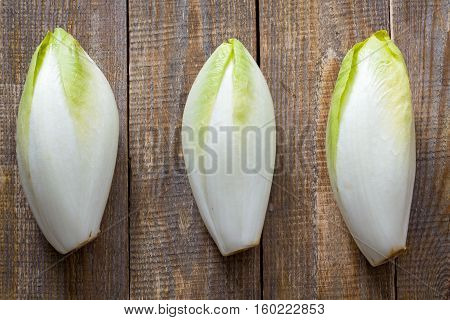 Top view on endive lying on wooden background.