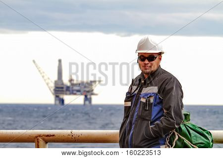 Oilman shift workers on the deck of the ship on the background offshore oil shelf planforms. Work on the way to work.