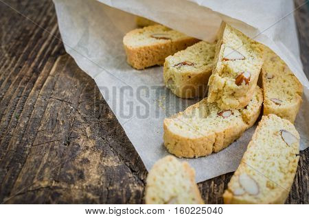 Italian cantuccini cookies with almond. Traditional italian almond cookies biscotti on old wooden background. Homemade Almond cookies on wooden table. Delicious cookies biscotti. Selective focus.