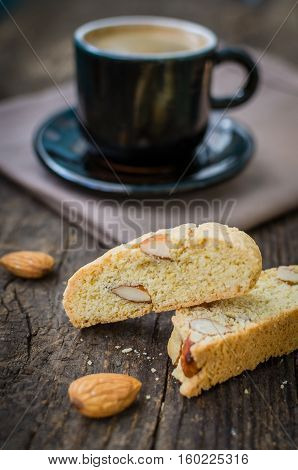 Good morning concept - breakfast frothy espresso coffee accompanied by delicious Italian almond cantuccini biscuits. Traditional italian biscotti cantuccini on wooden table. Selective focus.