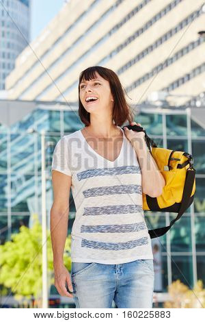 Happy Older Woman Carrying Duffel Bag Over Shoulder