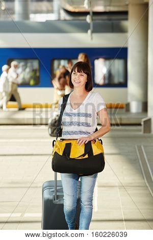 Female Traveler With Duffel Bag And Suitcase At Train Station