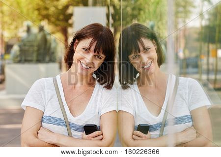 Close up portrait of smiling older woman leaning against reflection in building outside