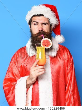 handsome bearded santa claus man with long beard on serious face holding glass of nonalcoholic cocktail in red christmas or xmas sweater and new year hat and drink on blue studio background