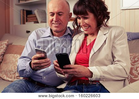 A mid shot of a couple sitting on the settee and gazing their devices, grinning from ear to ear, spending time with joy and pleasure. A few books in the cabinet behind them