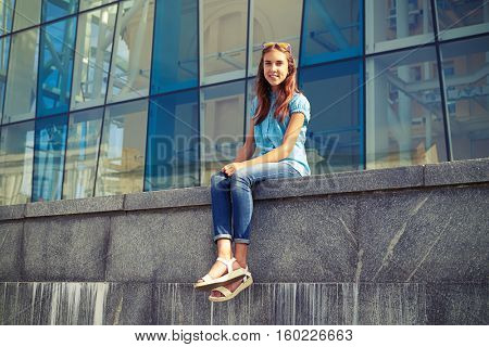Slim young girl in casual clothes sitting against a business center in the heart of downtown