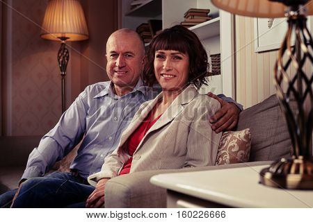 A mid shot a pair of sweethearts sitting on the couch and having their photo taken.A male wearing blue shirt and dark jeans embracing his lady