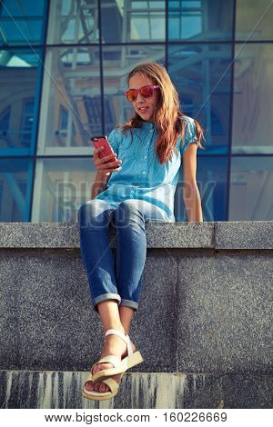 Smiling girl holding a phone while sitting on the concrete bench in the downtown. Relaxed and pleased in the hustle and bustle of the city