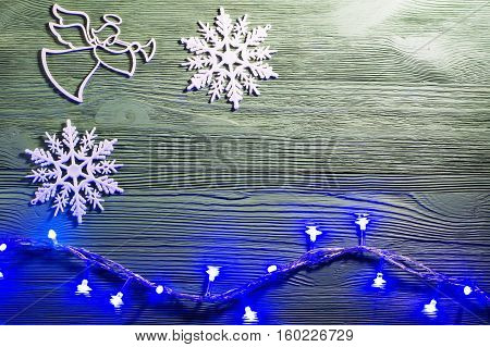 Christmas angel with wings and trumpet on cloud heralds the arrival of Christmas. Angel and snowflakes on wooden background flat lay. Christmas background with garland lights