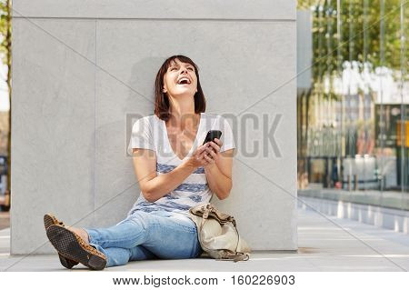 Laughing Older Woman Sitting On Ground With Purse And Phone